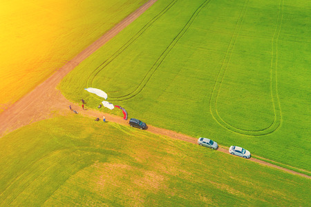 Top view of the people are preparing to fly on paragliders on the green field in the sunlight Stock Photo