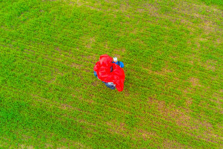View from the drone of the man with a red paraglider on a green field Фото со стока