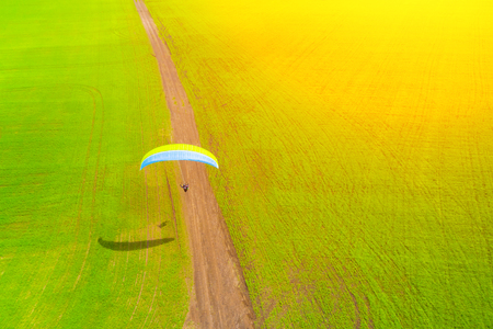 View from the drone of the man takes off from the field on a paraglider Stock Photo