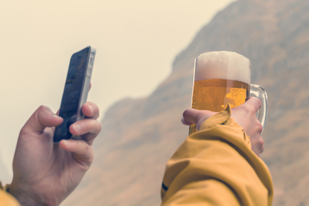 Man in a yellow jacket takes a beer mug on his phone Stock Photo - 106389317