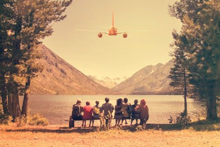 Airplane flying over a group of tourists sitting on a bench and looking at a lake in the mountains