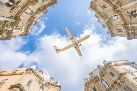 A view from the bottom up on historical Italian buildings and a flying plane Reklamní fotografie