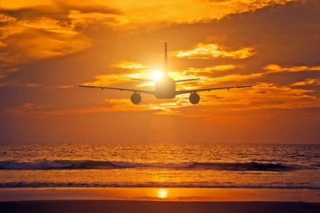 Airplane flying over the sea during sunset