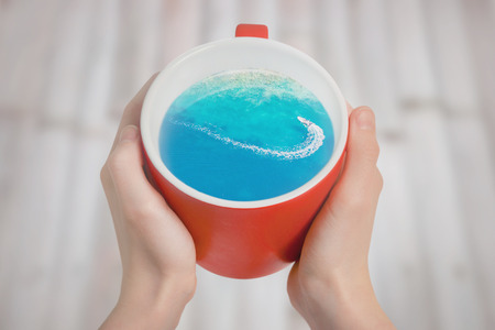 Red cup of coffee with the motor boat in the sea inside. Creative idea