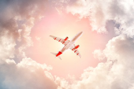 Airplane flying in the cloudy sky, bottom view Reklamní fotografie
