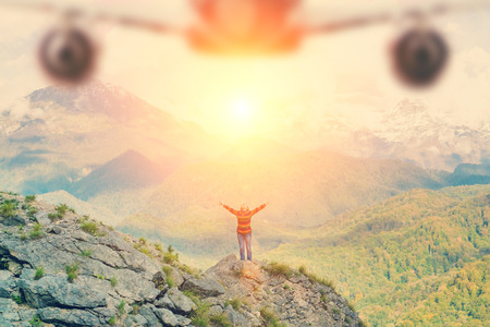 Woman in the mountains waves her hands to airplane