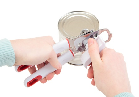 Womens hands with a  tin-opener open a tin photo