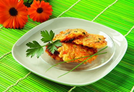 Pancakes with vegetables - zucchini, potatoes, carrots, onion and parsley photo