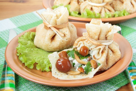 Bags of pancakes stuffed with mushrooms and chicken photo