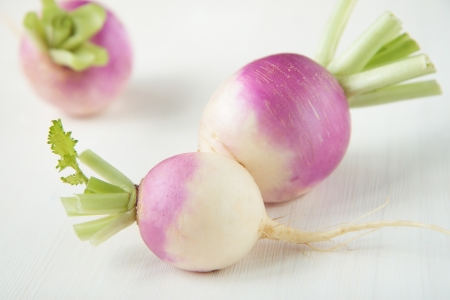green and purple vegetables: Three turnips with purple skin on table