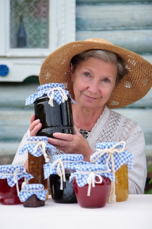 Elderly woman in a straw hat  holds a jar of homemade jam
