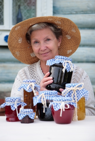 Elderly woman in a straw hat  holding a jar of homemade jam