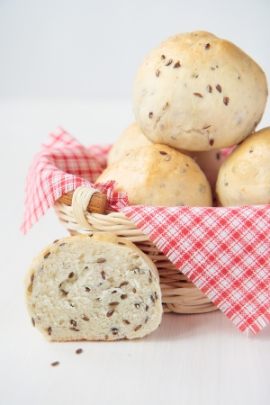 Freshly baked buns with flax seeds in basket Stock Photo - 15648340