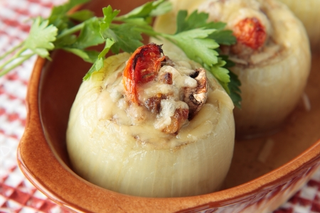Two onions stuffed with mushrooms, tomatoes and minced meat Stock Photo