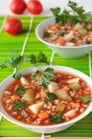 tomato paste: Soup with pickled cucumbers, barley  and tomato paste in bowl