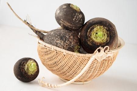 Several black radish root vegetables in a basket Standard-Bild