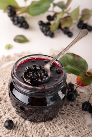 Black chokeberry jam in a small glass jar Standard-Bild