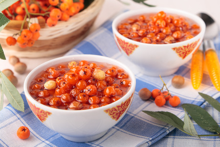 hazel branches: Two bowls of jam with rowan and hazel nuts Stock Photo