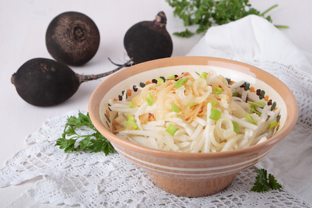 Black radish salad with fried onions in a ceramic bowl