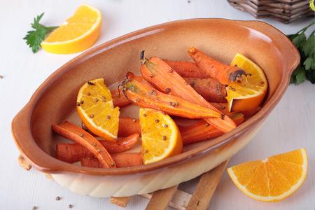 Carrots baked with orange and coriander in ceramic baking dish Standard-Bild