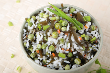 Salad of rice, laminaria, green peas, carrots and onions in a bowl