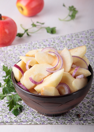 Salad with apples and red onions and oil in a ceramic bowl