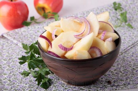 Salad with apples and red onions and oils in a ceramic bowl Standard-Bild