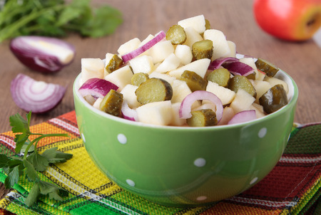 Salad with apples, pickled cucumbers and red onion in a bowl