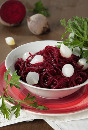 Braised beets with small pickled onions and parsley in a bowl Standard-Bild