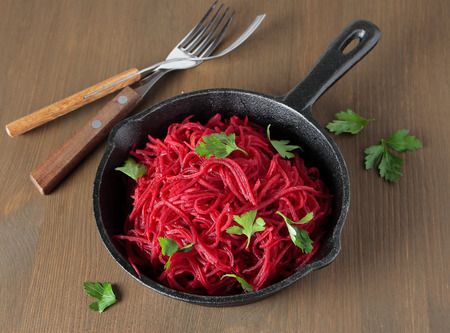 A cast iron pan with braised beetroot and parsley Standard-Bild
