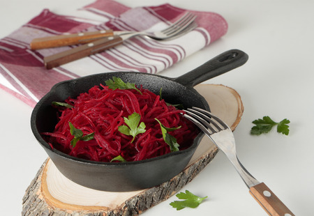 A cast iron pan with braised beetroot and parsley Stock Photo