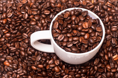 large bean: Closeup of white coffee cup full of coffee beans