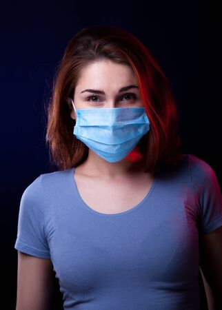 Portrait of confident woman wearing medical protective mask. Studio shot. Black background