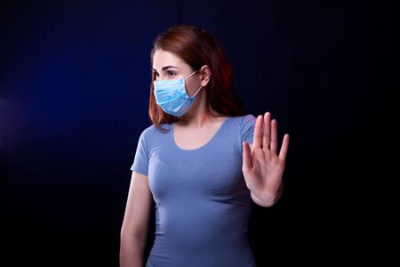 Young confident woman in medical protective mask shows STOP sign. Studio photo