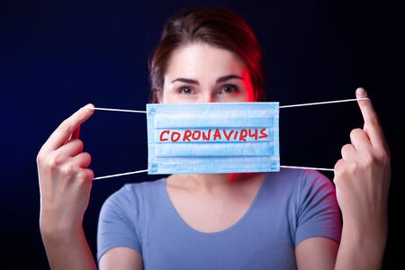 Young woman holding face protective mask with written coronavirus word. Studio shot. Stok Fotoğraf