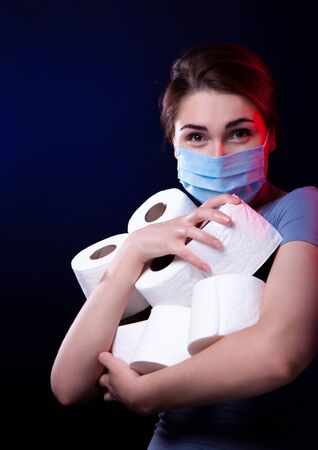 emotional young woman wearing protective mask with stock of toilet paper getting ready for quarantine. coronavirus panic