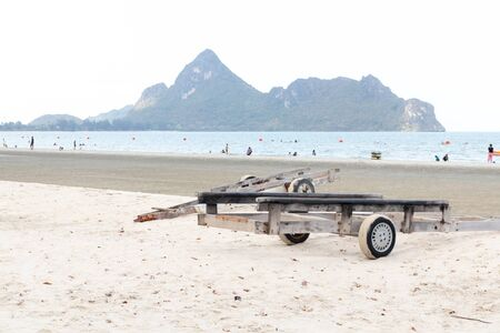 Boats trolley aground on the beach with mountain in the background.