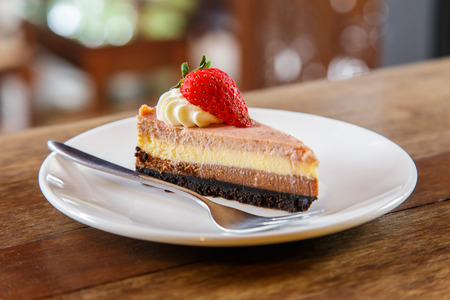 Slice of muti layer cheese cake with strawberry on the wooden table Stock Photo