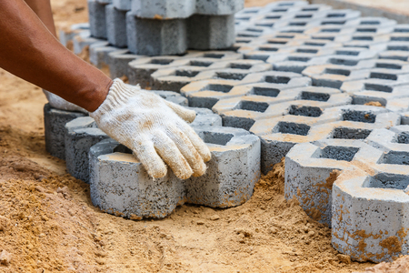 pavers: Construction worker paving new parking places, paving block turf stone Stock Photo