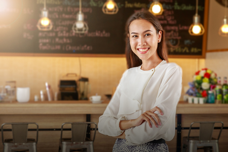 Portrait of happy young business owner with coffee shop background