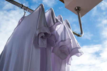 White T-shirts on clothesline against blue sky.