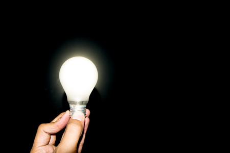glowing light bulb: Glowing light bulb on hand on white background. Stock Photo