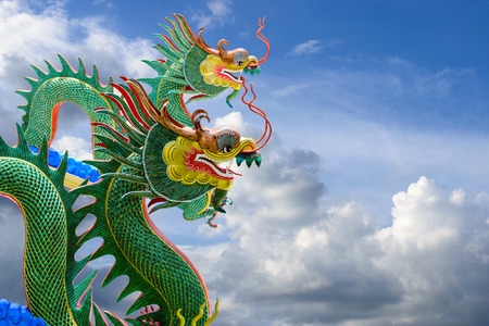 multiples: Green dragons on beautiful blue sky background.