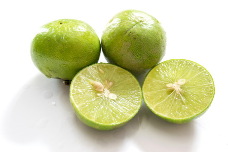 acidic: A green, oval citrus fruit with thick skin and fragrant, acidic juice. Stock Photo