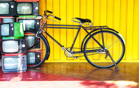 velocipede: Vintage bicycle and old TV on yellow wall background. Stock Photo