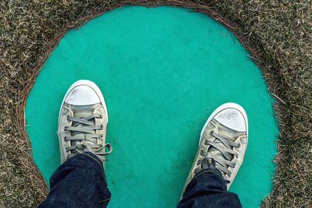 stepping: Man wearing blue jeans, sneakers and stepping on the circle.