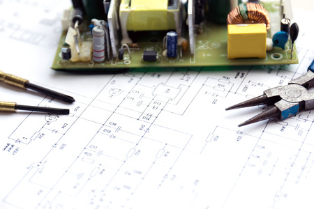 electrical component: Printed circuit board with electrical component and precision tools lying on construction drawing of electronics. Stock Photo