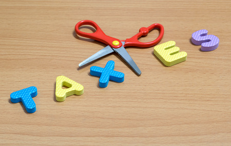 price cutting: Scissors and the plastic alphabet TAXES on wood background for business finance and accounting concept. Stock Photo