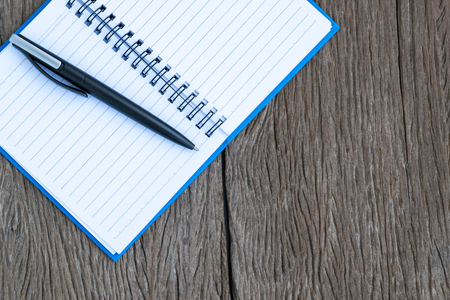 blank page: Place the pen on a blank page of a notebook on old wooden background. Stock Photo