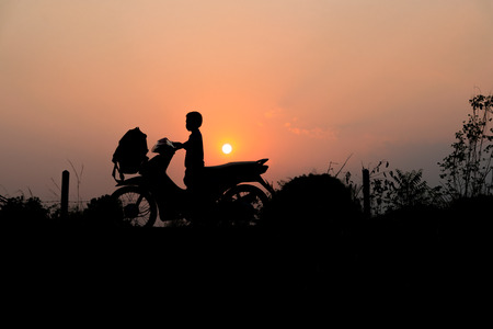 touring: Silhouette of motorcycle with the boy on beautiful sunset background.